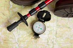 Het kompas op een kaart met een wandeling plakt en laarzen Royalty-vrije Stock Afbeeldingen