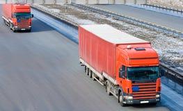Het konvooilijn van de twee rode vrachtwagenscaravan van de tractoraanhangwagen Royalty-vrije Stock Fotografie