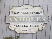 Het koop-verkoop teken van handelsantiquiteiten collectibles op grijze muur royalty-vrije stock fotografie