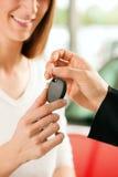 Het kopen van de vrouw auto - sleutel die wordt gegeven Royalty-vrije Stock Afbeeldingen