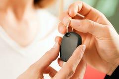 Het kopen van de vrouw auto - sleutel die wordt gegeven Stock Foto