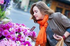 Het kopen van de vrouw bloemen bij markt Stock Afbeelding