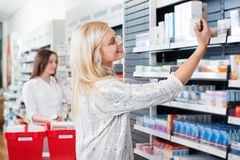 Het Kopen van de vrouw Geneeskunde in Apotheek Royalty-vrije Stock Afbeelding