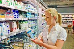 Het kopen van de vrouw melk bij de kruidenierswinkel Stock Foto