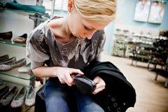Het kopen van de vrouw schoenen in een opslag Royalty-vrije Stock Foto's