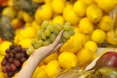Het kopen van druiven in een supermarkt Stock Fotografie