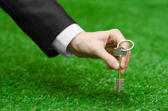 Het kopen van een nieuw huis of land en een bedrijfsonderwerp: dien een zwart kostuum in houdend een sleutel aan het nieuwe huis  Stock Afbeeldingen