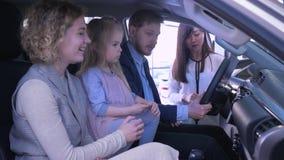 Het kopen van familievervoer, jong paar met leuk jong geitjemeisje communiceert over aankoopauto met verkopersadviseur terwijl stock videobeelden