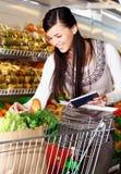 Het kopen van goederen in supermarkt Stock Foto