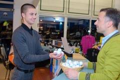 Het kopen van golfballen bij opslag Stock Foto's