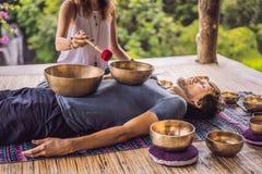 Het koper zingende kom van Nepal Boedha bij kuuroordsalon Jonge mooie mens die de zingende kommen van de massagetherapie in het K stock foto's