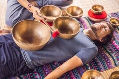 Het koper zingende kom van Nepal Boedha bij kuuroordsalon Jonge mooie mens die de zingende kommen van de massagetherapie in het K royalty-vrije stock fotografie