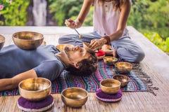 Het koper zingende kom van Nepal Boedha bij kuuroordsalon Jonge mooie mens die de zingende kommen van de massagetherapie in het K royalty-vrije stock afbeeldingen