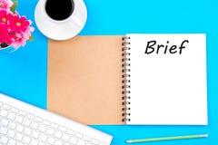 Het korte woord op notitieboekje met glazen, het potlood en de koffie vormen op houten lijst tot een kom Bedrijfs concept stock fotografie