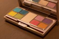Het kosmetische poedervakje plaatste velen kleur op houten lijst stock foto