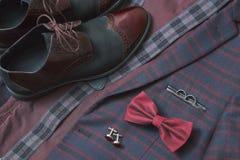 Het kostuum van mensenbourgondië, vlinderdas en uitstekende leerschoenen op textieltweedachtergrond Stock Foto