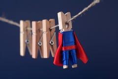 Het krachtige karakter van de supersterpin in blauwe kostuum rode kaap leiding en houten wasknijpersteam op het werk Donkere acht Stock Foto
