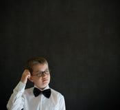 Het krassen van hoofd denkende jongen kleedde zich omhoog als bedrijfsmens Royalty-vrije Stock Afbeeldingen