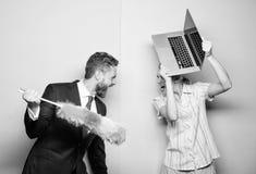Het krijgen op een strijd Echtgenoottribune met stofborstel terwijl laptop van de vrouwenholding Paar van de knappe mens en mooie stock fotografie
