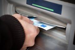 Het krijgen van contant geld bij ATM-machine Stock Foto's