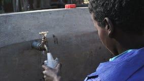 Het krijgen van water van een kraan stock videobeelden