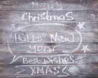 Het Krijtinschrijvingen van het Kerstmis Nieuwe jaar op de houten achtergrond royalty-vrije stock foto