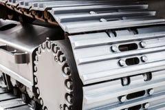 Het kruippakje volgt hydraulica op een tractor of een graafwerktuig stock afbeelding