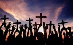 Het Kruis van de groeps Mensen Holding en het Bidden in Achterlit stock afbeeldingen