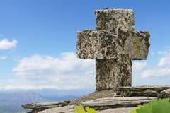 Het kruis van de steen bij een bergpiek Stock Fotografie