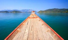 Het kruisen met houten boot in duidelijke blauwe hemel stock foto