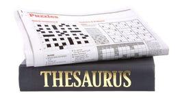 Het kruiswoordraadsel van de krant bovenop een thesaurus Stock Foto's