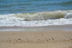 Het krullen in golf door het strand Royalty-vrije Stock Fotografie