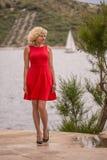 Het krullende blondemeisje in rode kleding bevindt zich dichtbij van het overzees Royalty-vrije Stock Afbeeldingen