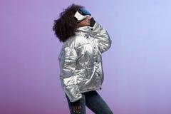 Het krullende bruin-haired meisje van mod. gekleed in een zilveren-gekleurd jasje gebruikt de virtuele werkelijkheidsglazen in de royalty-vrije stock foto