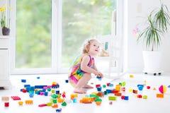 Het krullende het lachen peutermeisje spelen met kleurrijke blokken Royalty-vrije Stock Foto's