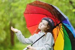 Het krullende kind geniet van om regen in openlucht op te springen stock afbeeldingen
