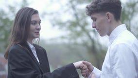Het krullende mannetje kust hand van wijfje het in openlucht Jonge paar tijd samen koppelt in liefde Gelukkig paar doorbrengt stock footage