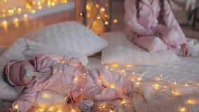 Het krullende meisje en haar pasgeboren kleine zuster op witte plaid breiden samen warme zachte lichten rond hen stock footage