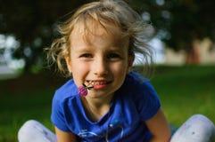 Het krullende meisje met lichtbruin haar zit op het gras Zij houdt een purpere klaverbloem in haar mond De babyglimlachen Stock Afbeelding