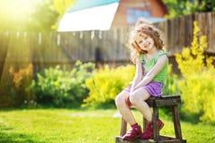 Het krullende meisje zit op een stoel in de werf van een buitenhuis Stock Afbeelding
