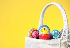 Het kuiken van Pasen dat op eishell wordt geschilderd die uit gluurt stock foto