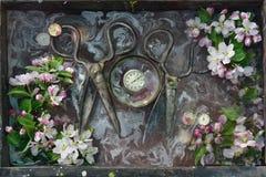 Het kunststilleven met twee paar van oude reusachtige roestige schaar, tussen de schaar ligt de oude chronometer in de ronde kom, Stock Afbeeldingen