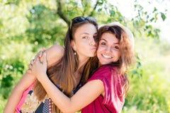 Het kussen pret: donkerbruine jonge vrouwen beste vrienden die blije tijd hebben die & camera op groene su lachen bekijken Stock Afbeelding