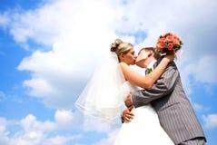 Het kussen van de bruid en van de bruidegom tegen blauwe hemel Royalty-vrije Stock Foto's