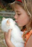 Het kussen van het meisje katje Stock Foto