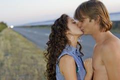 Het kussen van het paar bij de rand van weg royalty-vrije stock fotografie