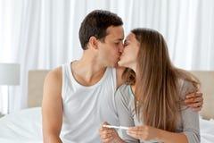 Het kussen van het paar na het bekijken een zwangerschapstest Stock Afbeeldingen