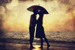 Het kussen van het paar onder paraplu bij het strand in zonsondergang. Foto in o Stock Fotografie