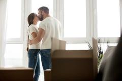 Het kussen van jong paar in nieuwe flat met uitgepakte bezittingen stock fotografie