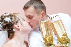 Het kussen van onlangs-Gehuwd paar met champagne Stock Foto's